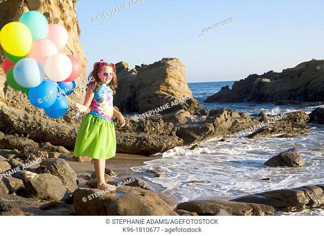 young girl in green skirt standing on rocks at the beach holding balloons