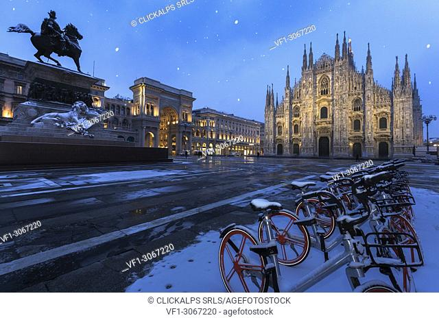 Bicycles parked in PIazza Duomo during snowfall at dusk. Milan, Lombardy, Northern Italy, Italy