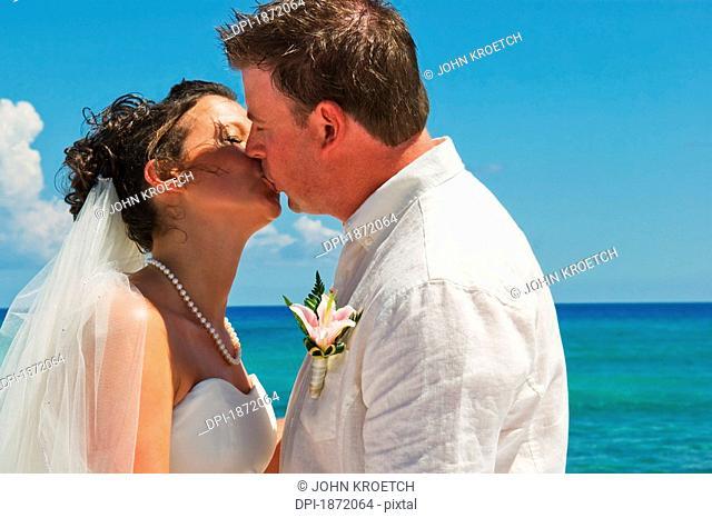 akumal, riviera maya, mexico, a bride and groom kiss on the beach at gran bahia principe tulum all-inclusive resort