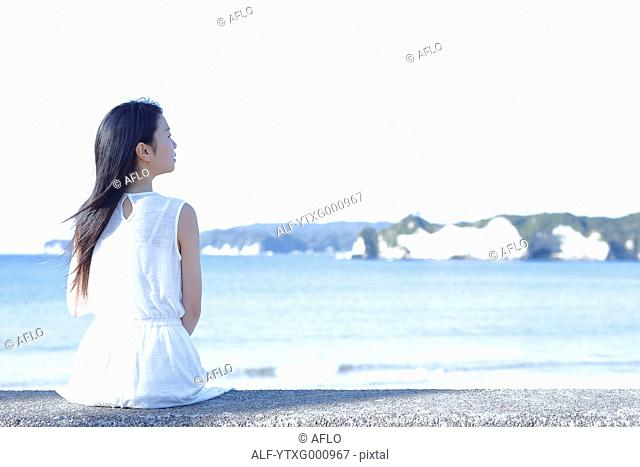 Young Japanese woman in a white dress by the sea, Chiba, Japan