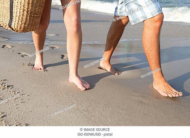 Legs of couple walking on beach