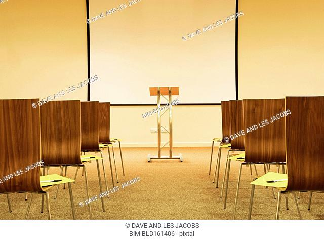 Empty chairs and podium with screen in presentation room