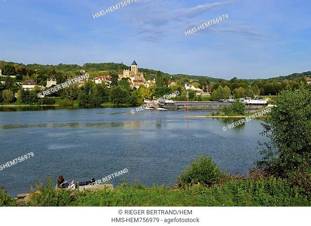 France, Val-d'Oise, a barge on the Seine river in front of Vetheuil and its Notre Dame church painted by Claude Monet