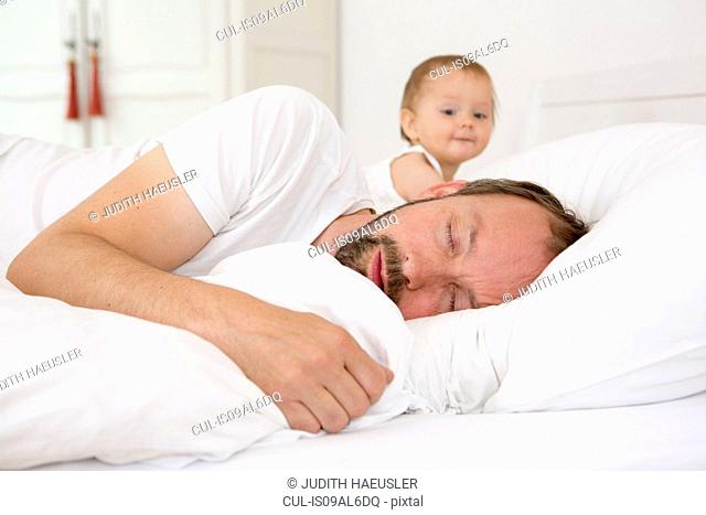 Father asleep in bed, baby daughter watching