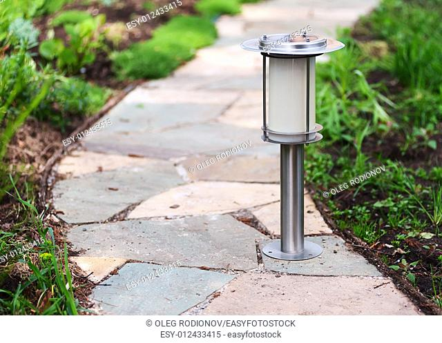 Solar-powered lamp on garden path. Nature background. Selective focus