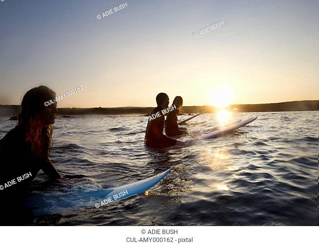 Four people sitting on surfboards in the water smiling