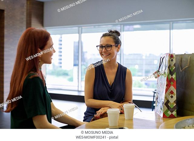 Girl friends on a shopping spree meeting in a coffee shop