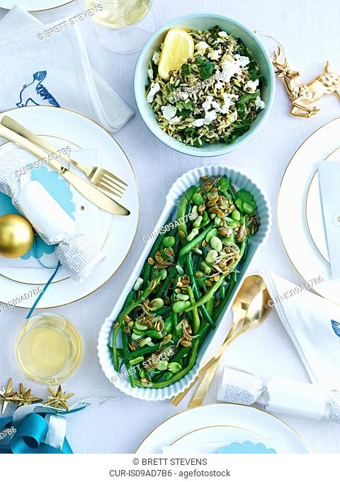 Dishes of lemon orzo and green beans on decorated table