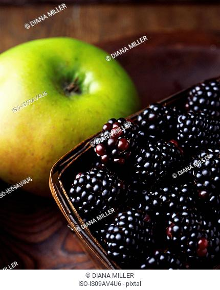 Close up of green apple and blackberries in wooden basket