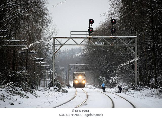 Workers clear snow from a track switch as an Amtrak Cascades train waits, Burnaby, British Columbia, Canada