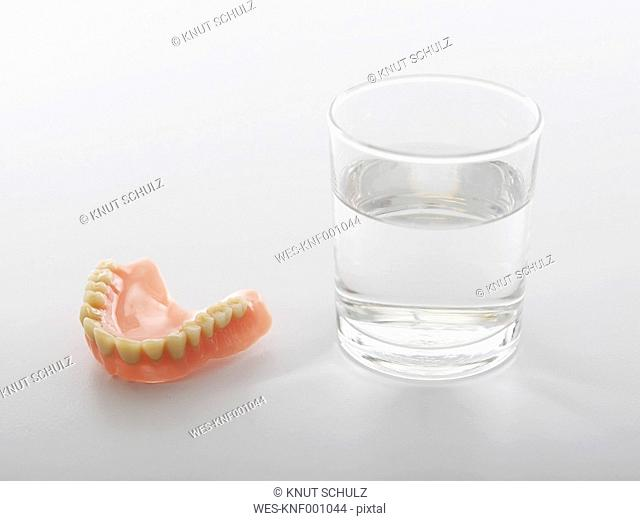 Dentures with water glass on white background
