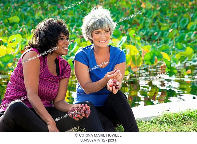 Mature female friends sitting in park, eating grapes