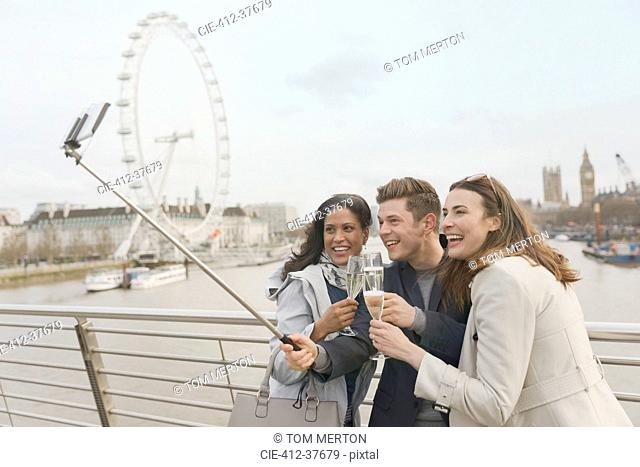 Smiling friend tourists celebrating, toasting champagne and taking selfie with selfie stick near Millennium Wheel, London, UK