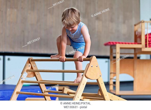 Boy three years climbing ladder in Gym