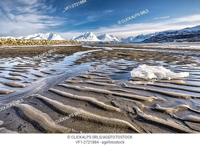 The icy sandy beach surrounding the snow capped mountains Breivikeidet Lyngen Alps Tromsø Lapland Norway Europe