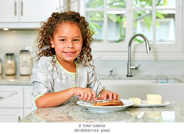Girl at kitchen counter spreading butter on toast looking at camera smiling