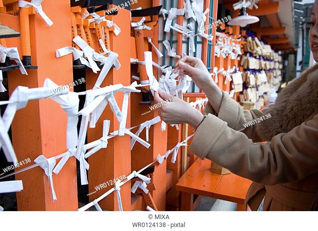Young woman tying fortune paper