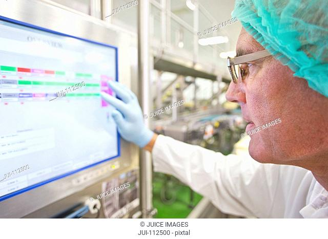 Close up machine operator watching computer monitor in cheese processing plant