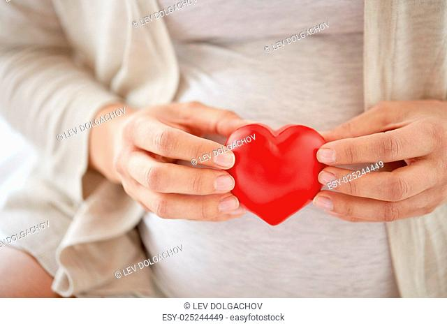 pregnancy, love, people and expectation concept - close up of pregnant woman with red heart