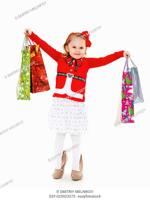 Happy pretty little child with shopping bags stands on a white background. 3 year old