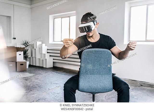 Man sitting on chair in empty loft wearing VR glasses