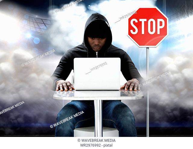Hacker working on laptop in front of stop board