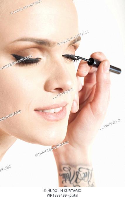 Makeup artist applying mascara, close-up