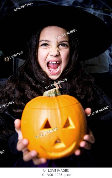 Girl in a witch's costume at a Hallowe'en party, holding a pumpkin with a carved face