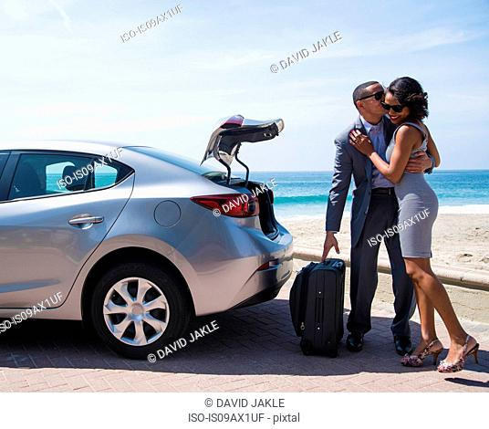 Honeymoon couple with luggage, kissing on beach