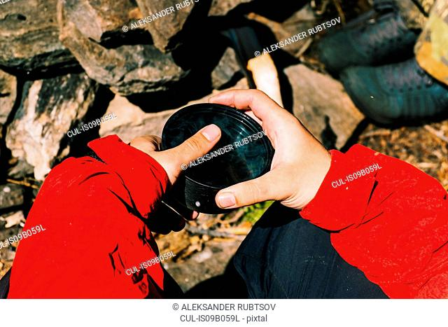 Hands of male hiker holding cup of tea, Russia