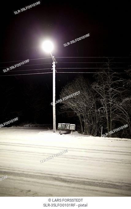 Streetlight over snowy road at night