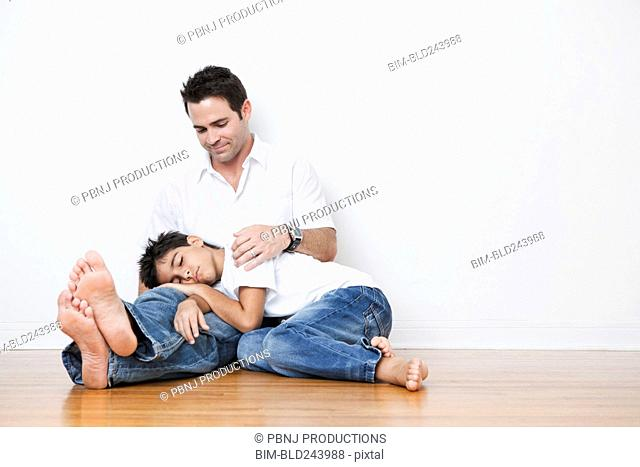 Mixed Race boy napping in lap of father on floor