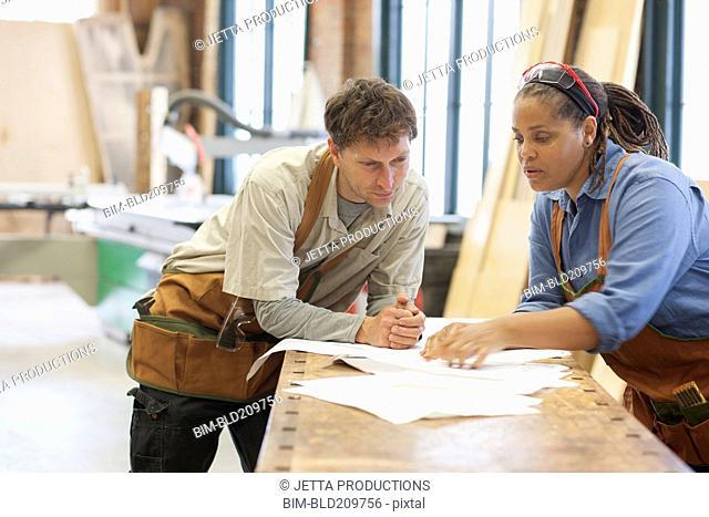 Carpenters looking at plans in workshop