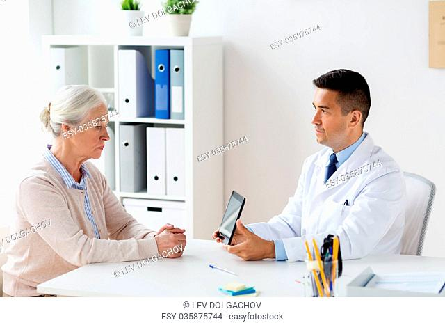 senior woman and doctor with tablet pc at hospital