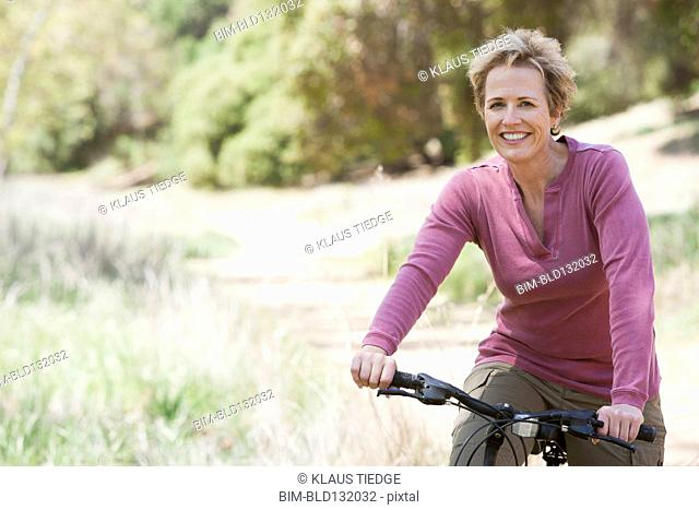 Senior Caucasian woman riding bicycle on rural path