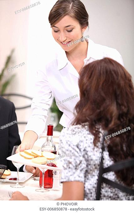 Waiter serving starters in a restaurant Stock Photos and