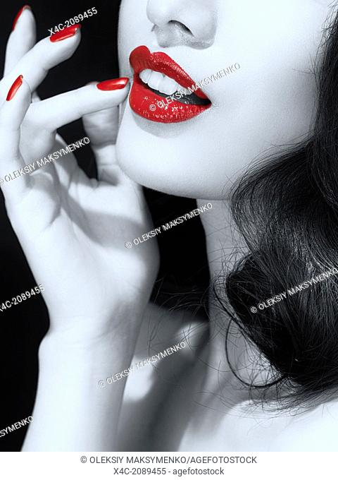 Artistic black and white portrait of a young woman's mouth with bright red lipstick