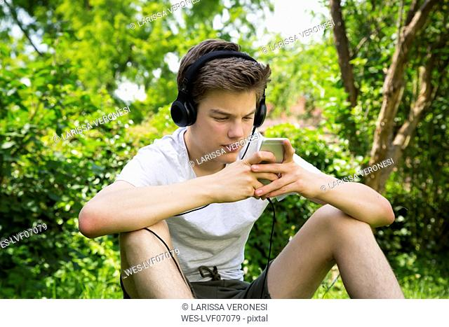 Boy sitting in the garden listening music with headphones and smartphone