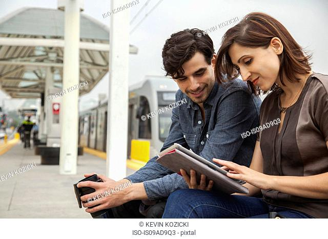 Couple reading newspaper whilst waiting at station, Los Angeles, California, USA
