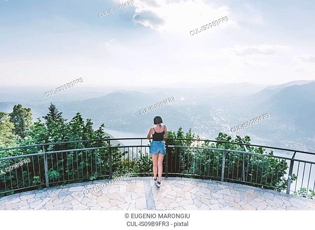 Rear view of young woman on viewing platform looking out at Lake Como, Lombardy, Italy