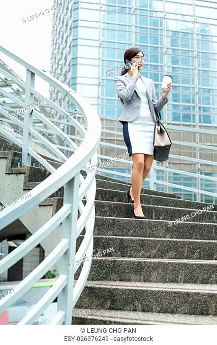 Businesswoman doing down stair in financial district at Hong Kong