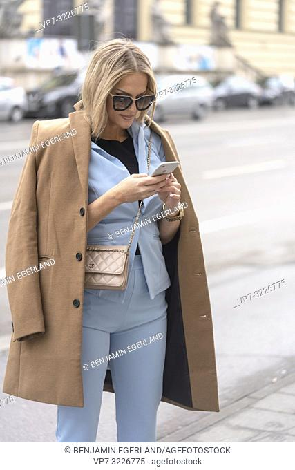 Fashionable woman using smartphone, Munich, Germany