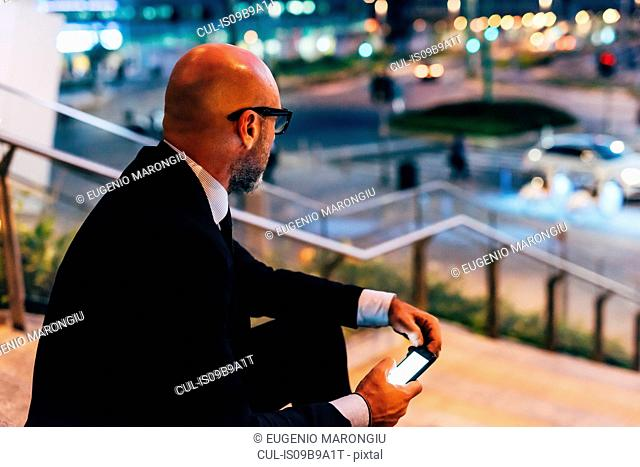 Mature businessman outdoors at night, sitting on steps, holding smartphone