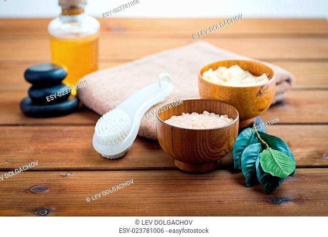 beauty, spa, body care, natural cosmetics and concept - close up of pink salt with massage oil and bath towel on wooden table