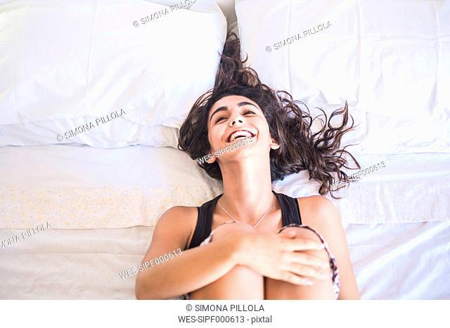 Laughing teenage girl lying on bed hugging knees