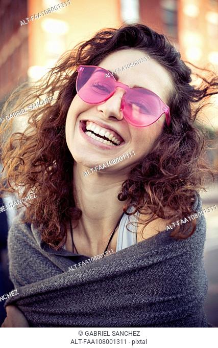 Woman wearing pink sunglasses, laughing, portrait