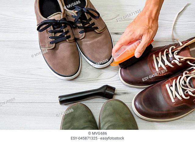 Man cleaning and polishing leather shoes with brush on wooden background