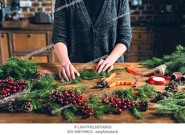 cropped view of decorator making Christmas wreath of fir branches, decorative berries and pine cones at workplace