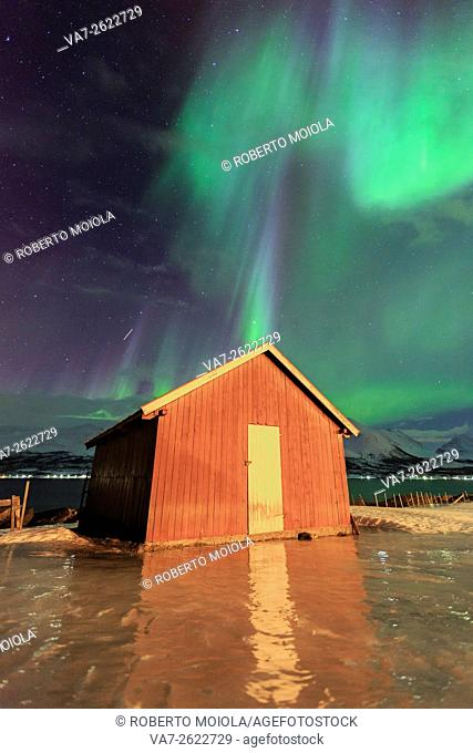 Northern Lights illuminates the wooden cabin at Lenangsoyra Lyngen Alps Tromsø Lapland Norway Europe