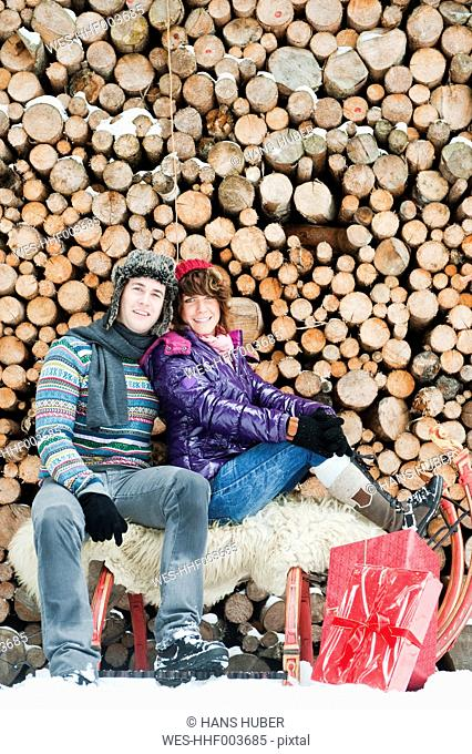 Austria, Salzburg Country, Flachau, Young man and woman sitting on sledge with christmas present and firewoods in background